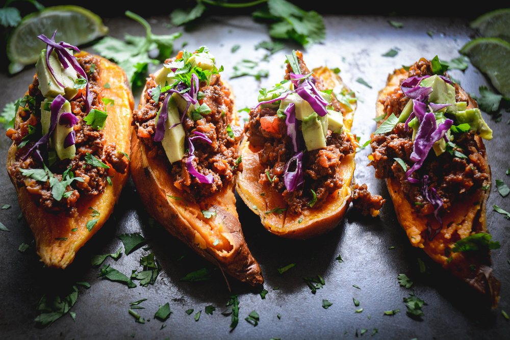 Four sweet potatoes, stuffed with chili on tray