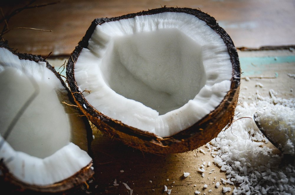 coconut halves on board, coconut flakes on spoon