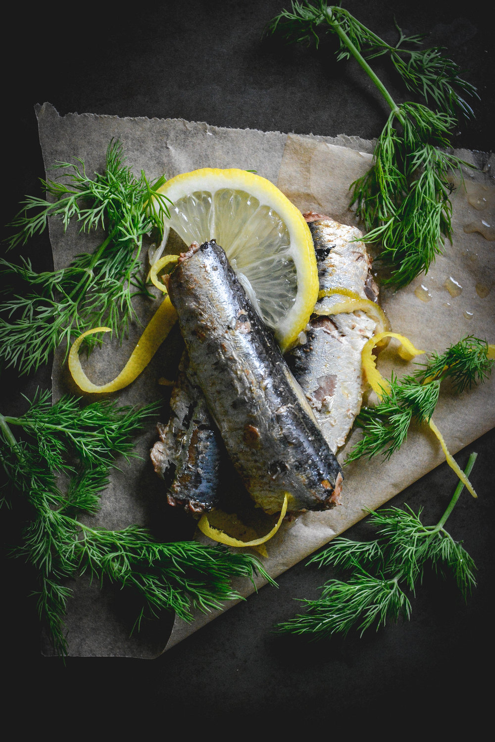 why do we need omega 3 fatty acids in the diet? sardines, dill and lemon on parchment paper