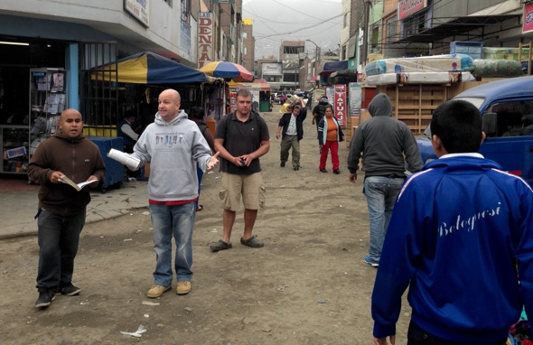 TJ preaches, Edher translates, Ricky distributes in a Lima street market