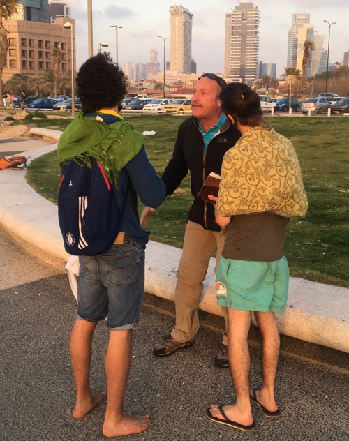 Brother Ken Lightsey engages some Israeli young men down on the Tel Aviv boardwalk.