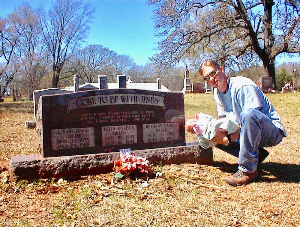 Jesse Boyd poses with Bethany Grace, his infant daughter, at the grave of Keith Green and his two children in Garden Valley, TX.
