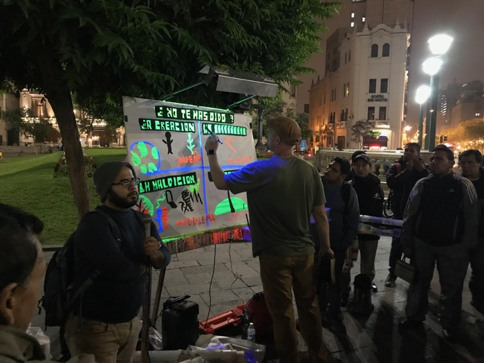 Jesse Boyd preaches in Plaza de San Martin with a Paintboard.