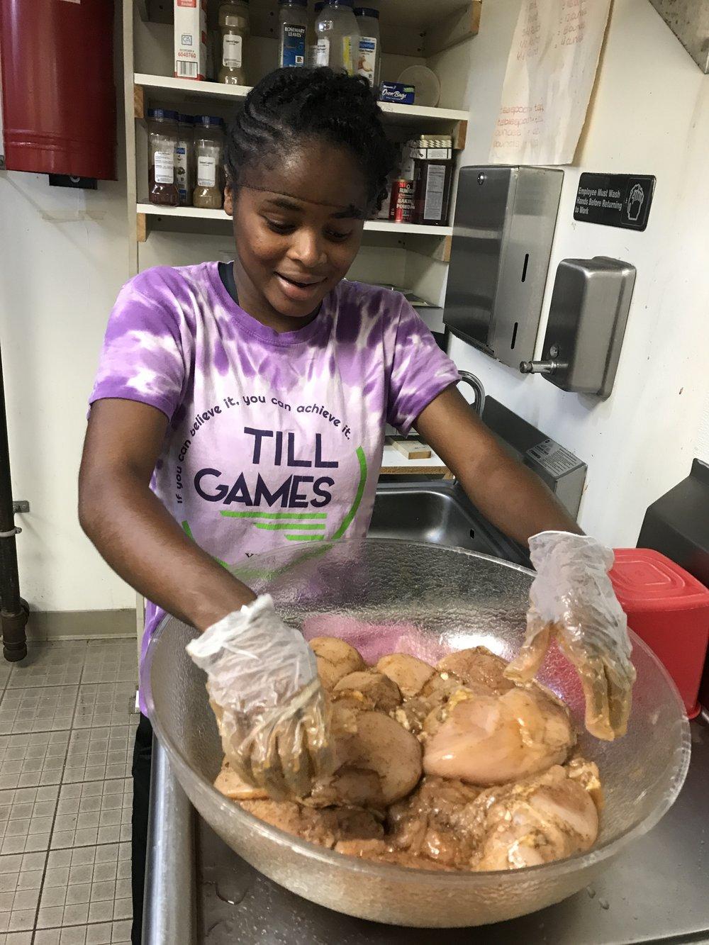 Arimayah '18 marinating the chicken.