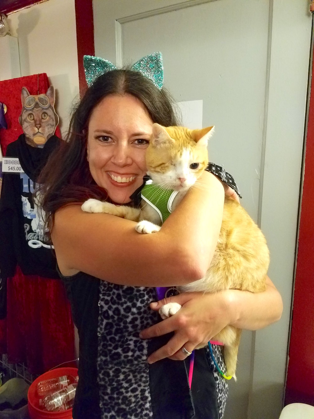 "Here's Debbie with her own furbaby, Captain Patch (who travels with the crew and is training to be the ""Merch Cat""!)"
