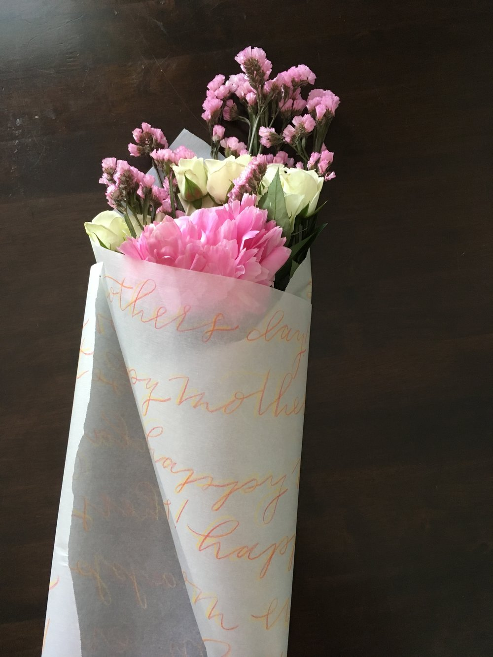 Step 8. - Roll the floral paper around the bouquet. Start at the lower right corner and tuck it over the stems and continue rolling the bouquet until you've reached the other side of the paper.