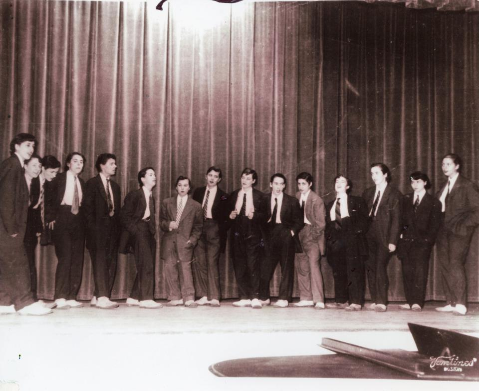 Dressed as Jabberwocks, the original Chattertocks perform in Alumnae Hall, 1952    Left to right:  Diane Aspinall Parker, '55 Marcia Searles Horn,'55 Barbara Schoen Silverman, '55 Sue Morgan Rolontz, '55 Marcia Pickering Hunt, '55 Lynne Johnson, '55 Bennie Saievetz Herman, '55 Judy Jackson Carroll, '55 Peggy Kelly, '55 Louise Harrington Thompson, '55 Lolly Moschos Lewry, '55 Nancy Tobin Dorer, '55 Roz Taylor, '55 Dolly Senerchia, '55 Diane Deliniks Schaumann, '55