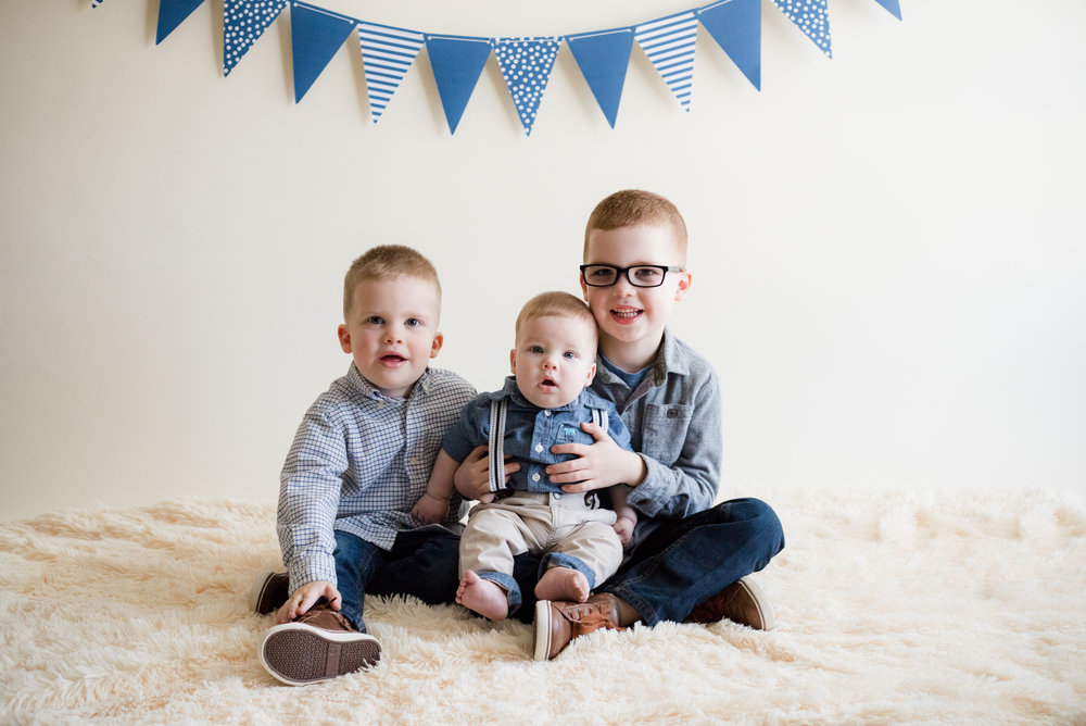 Three boys sitting during indoor photo session.