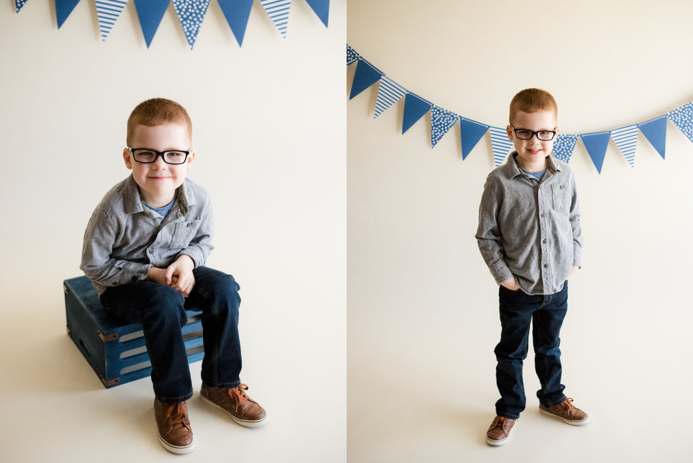 Five year old boy in blue sitting and standing during indoor photo session located in Cedar Rapids, Iowa.