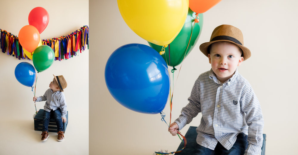 Three year old boy in hat holding balloons during indoor photo session in Cedar Rapids, Iowa.
