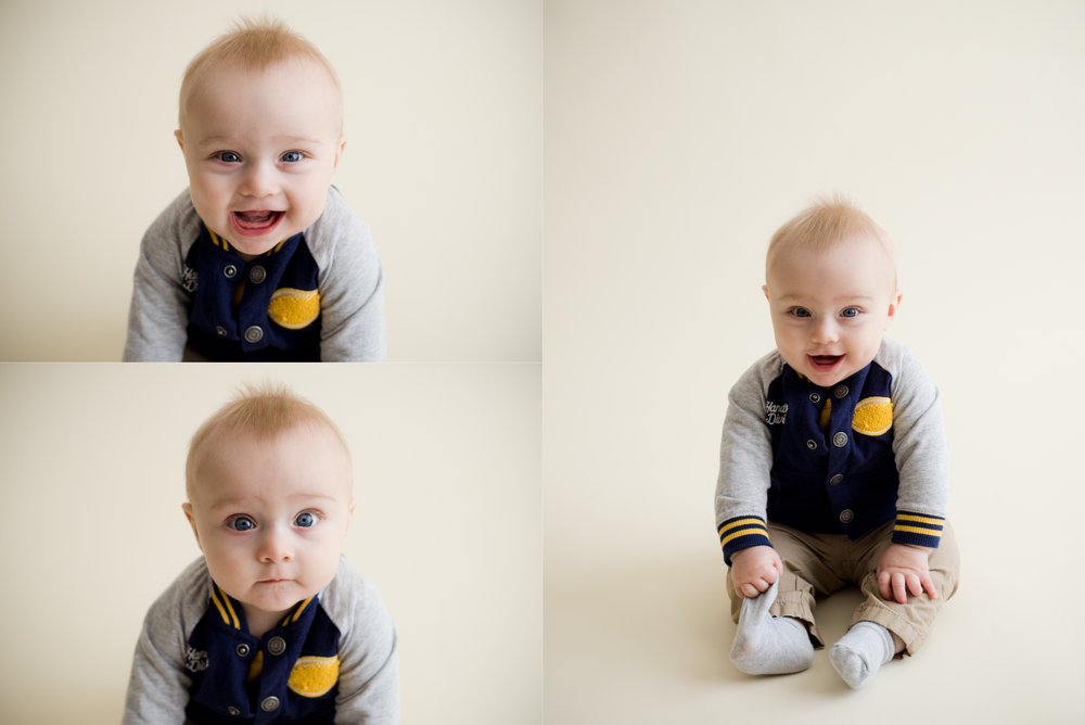 Six months old baby boy sitting and smiling during photo session in Cedar Rapids, Iowa.