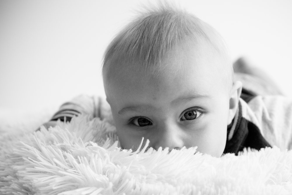 Baby boy looking at the camera laying down during photo session in Cedar Rapids, Iowa.