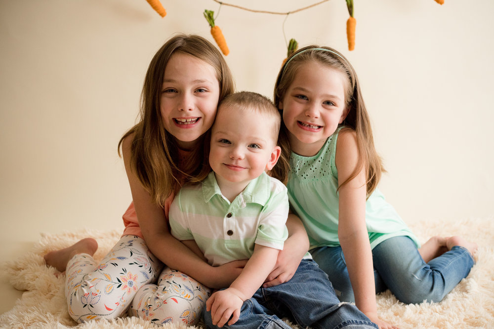 Two sisters and their little brother sitting and smiling in a photo during Easter Mini Session.