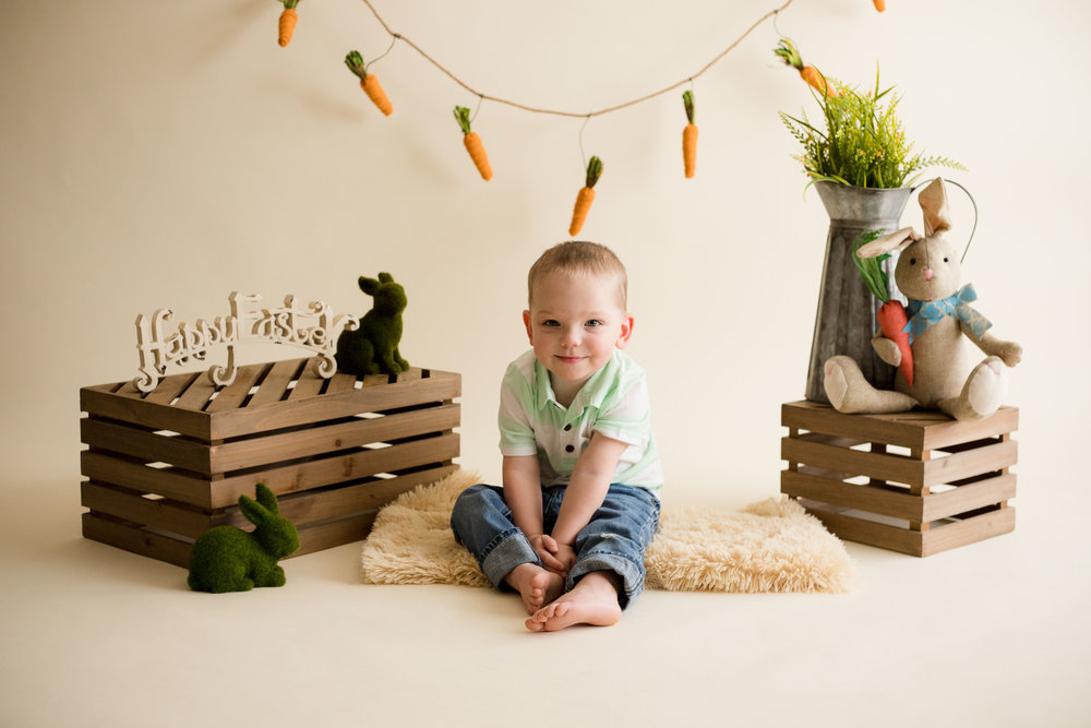 Two year old boy sitting and smiling at camera during indoor photo session.