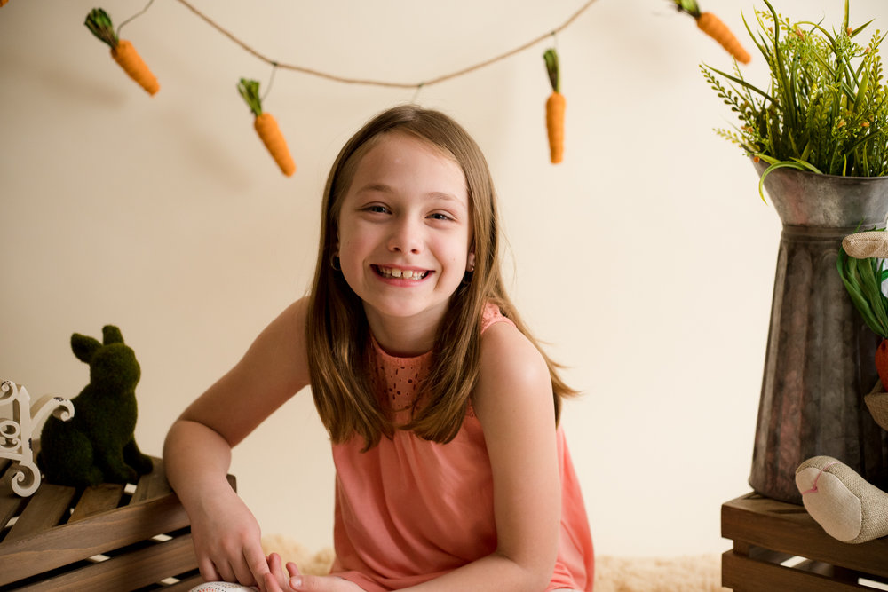 Seven year old girl smiling for the camera during indoor photo session.