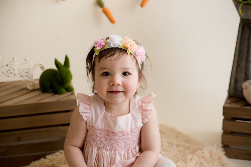 One year old girl sitting in pink dress and flower headband during photo session.