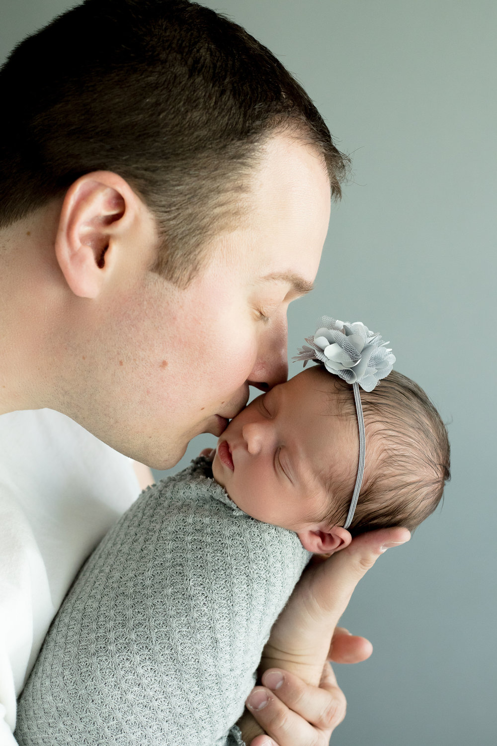 Father kissing newborn girl during newborn photo session in Cedar Rapids, Iowa.