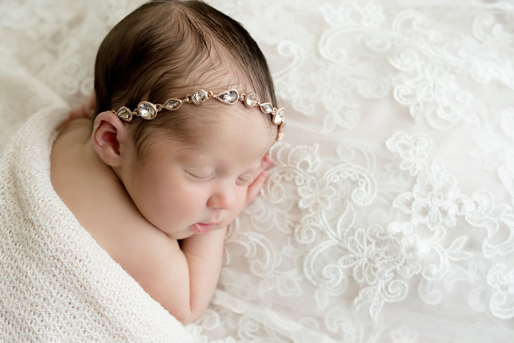 Six day old baby girl sleeping on mother's wedding dress at Laura Anne Photography.