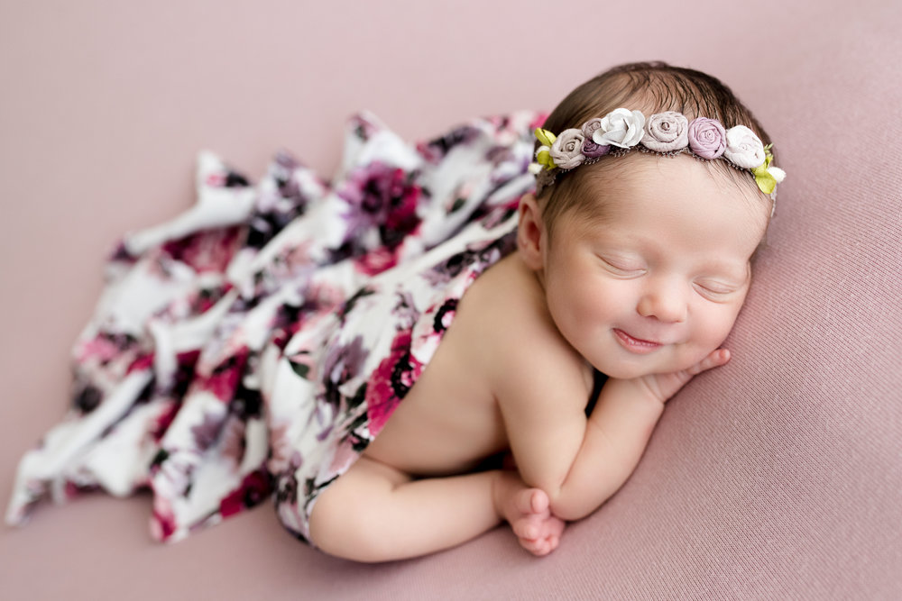 Baby girl smiling during newborn photo session in Iowa.