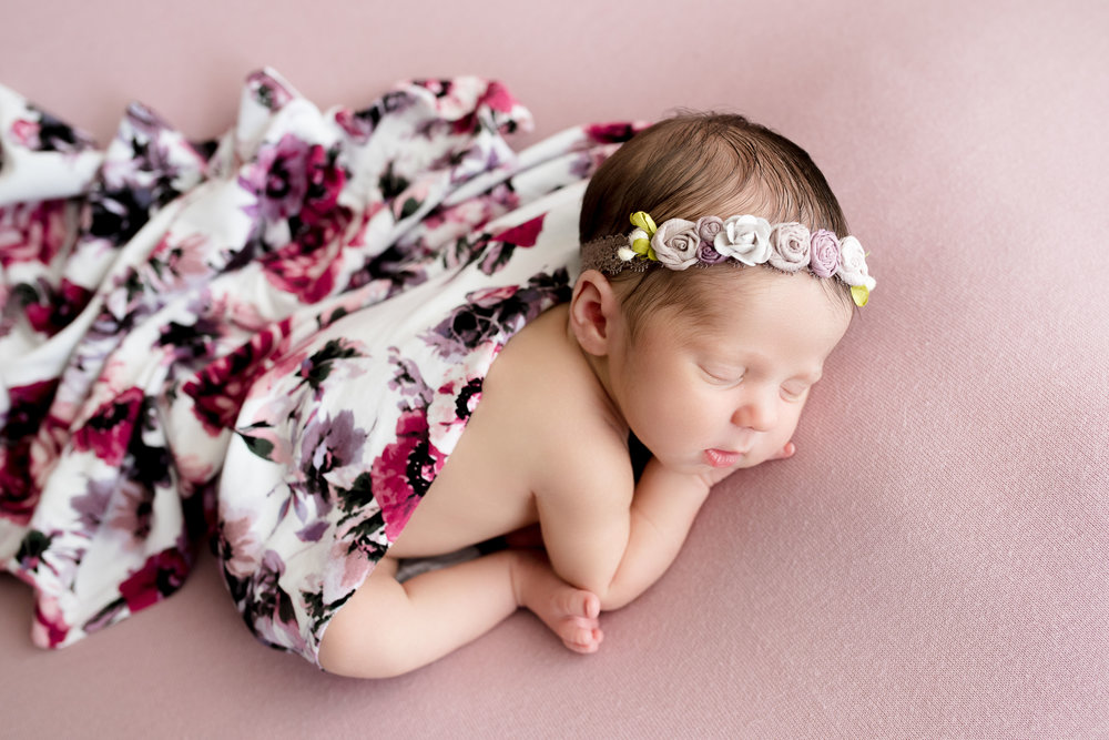 Six day old baby girl sleeping on pink blanket during newborn photo session in Iowa.