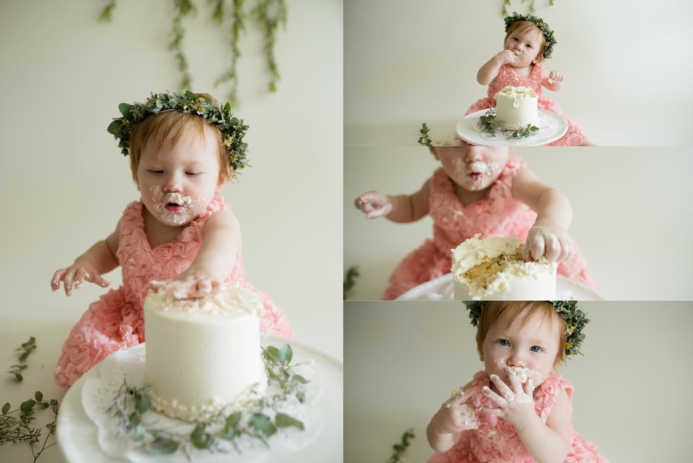 Baby girl smashing cake with hands and eating cake during cake smash photo session on southwest side of Cedar Rapids.