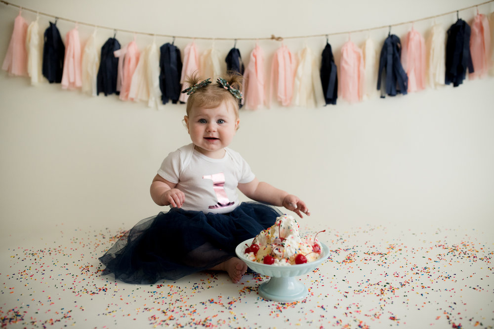 One year old baby girl sitting in front of ice cream during a sundae smash photo session with Laura Anne Photography  in Cedar Rapids, Iowa.