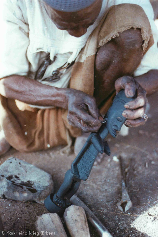 Tinnin Fané decorates the figure with a metal earring. Photo: Karl-Heinz Krieg, Fakola (Mali), 1981