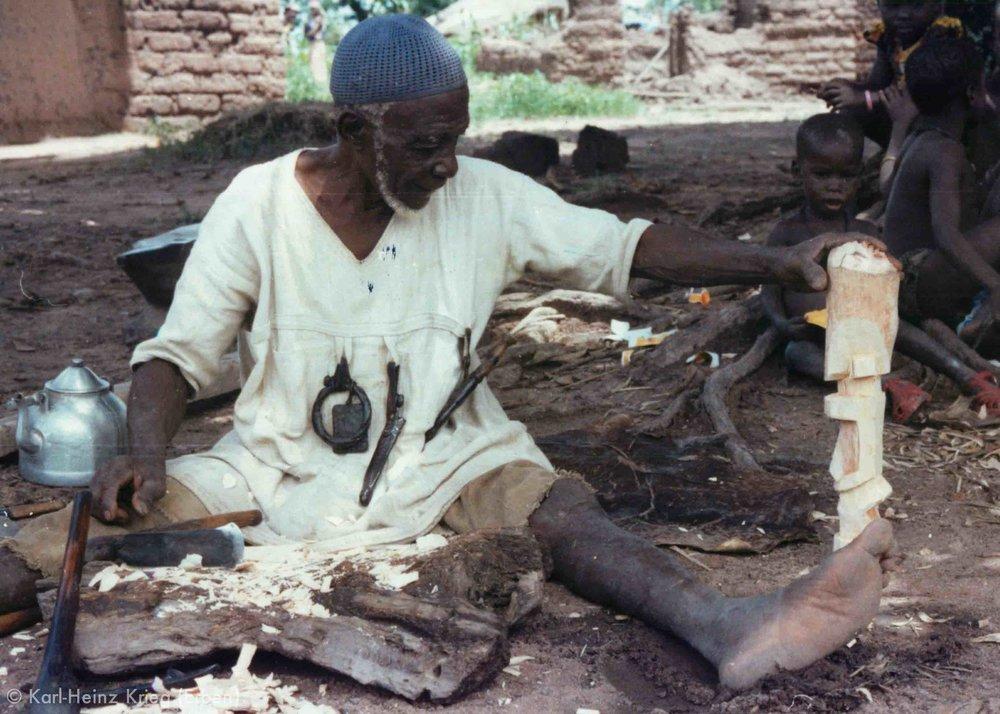 Tinnin Fané carves a wooden figure. Photo: Karl-Heinz Krieg, Fakola (Mali), 1981
