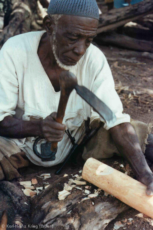 Tinnin Fané carves a figure from freshly cut wood. Photo: Karl-Heinz Krieg, Fakola (Mali), 1981