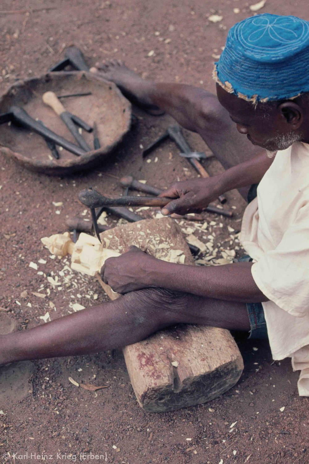 Songuifolo Silué uses his traditional carving tools to carve a small figure from freshly cut wood. Photo: Karl-Heinz Krieg, Sirasso (Region of Boundiali, Côte d'Ivoire), 1978