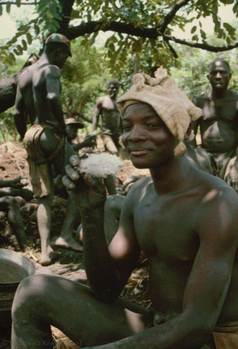 Mittagspause beim Feldbau-Wettbewerb in Kounoumon. Die  Plale  essen gerösteten Yams. Der junge Mann trägt eine baumwollene Jadmütze. Foto: Karl-Heinz Krieg, Kounoumon (Region von Boundiali, Côte d'Ivoire), 1980
