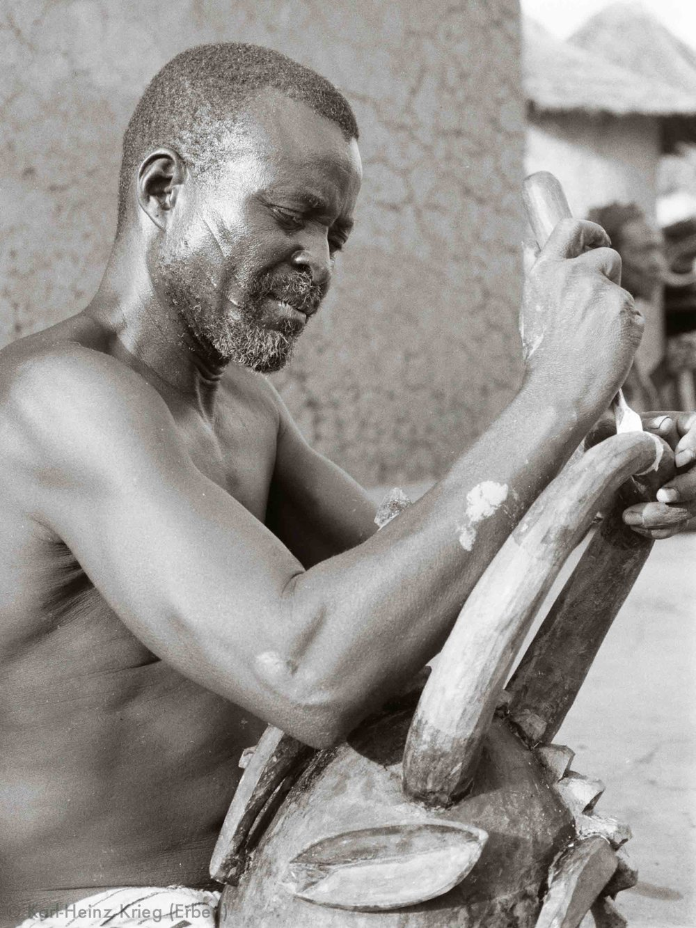 Karna Ouattara carving a helmet mask in his workplace. Photo: Karl-Heinz Krieg, Nafoun (Region of Boundiali, Côte d'Ivoire), 1975