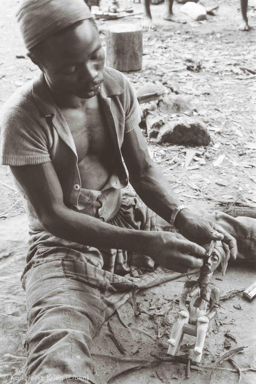 Sécondjéwin Dagnogo covering a newly carved figure with red pigment. Poundiou (Region of Boundiali, Côte d'Ivoire), 1975. Photo: Karl-Heinz Krieg