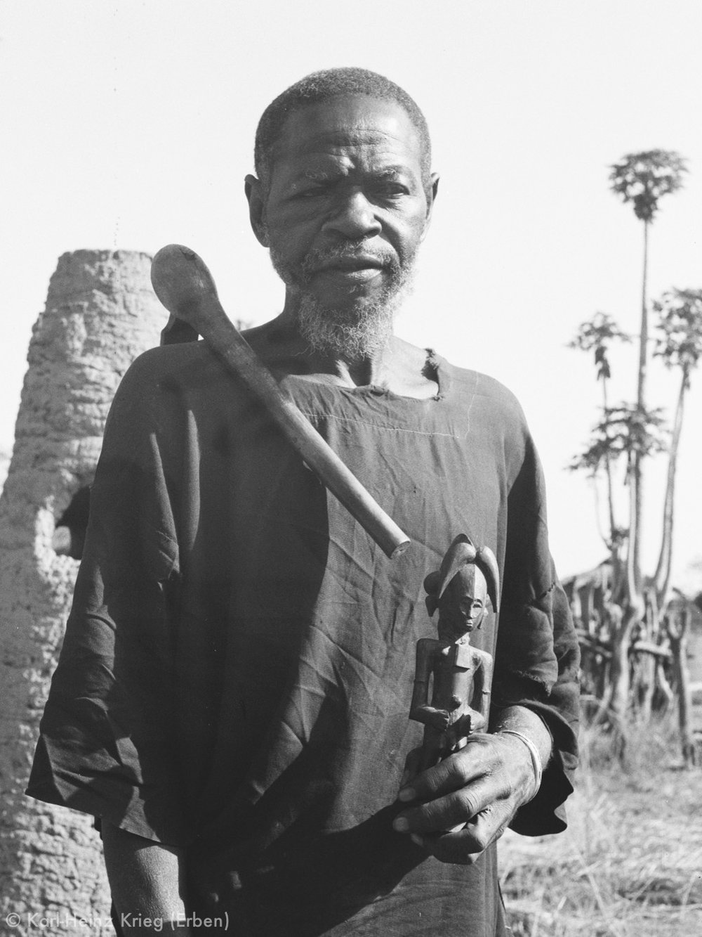Kolotielema Dagnogo with a figure that he carved. On his right shoulder he carries an  adze , the symbol of a wood carver. Behind him are old furnaces used to smelt iron in the past. Photo: Karl-Heinz Krieg, Poundiou (Region of Boundiali), 1974