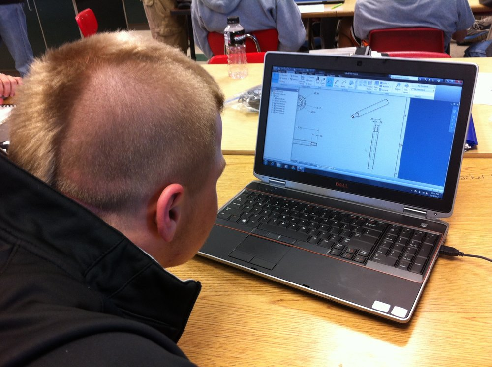 Engineering student using computer design software to create tools.