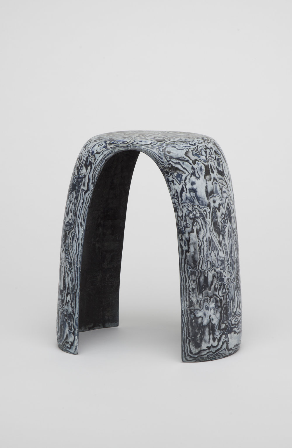 Bahia Stool:The Bahia stool is a sculptural seating piece for the interior. It is made out of denim offcuts from Diesels Denim-production. The disgards are draped over a mould and the layers are adhesed together with bioresin. After the material is dry it is carved to create a flat surface. Through the carving process as well as through the different sized and coloured offcuts a bespoke marble-like pattern appears. The arch shape of the stool forms an elegant and sculptural silhouette which is ideal to reveal the vibrant pattern of the Bahia Denim.The marble-illusion gave the stool its name, the Bahia Denim, named after a Brazilian blue marble which it resembles.