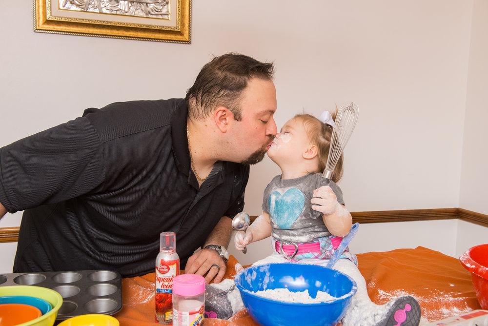 Messy toddler baking kiss father cake smash