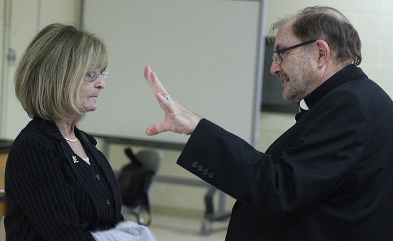 """Helen Konstance, a cantor at St. Martha Parish in Philadelphia, speaks with Franciscan Father Frank Berna after his Oct. 14 lecture entitled """"If Liturgy Were Like an Eagles Game."""" Sponsored by the Association of Church Musicians in Philadelphia, the presentation surveyed strategies for increasing engagement at Sunday Mass. (Photo by Gina Christian.)"""