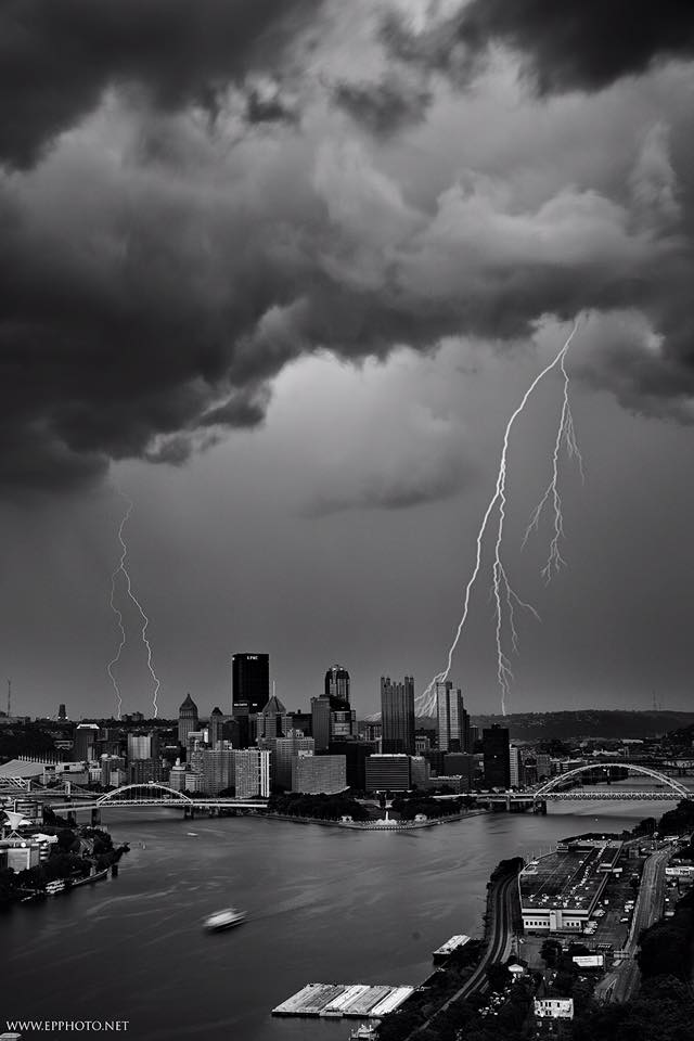 EMMANUEL'S COLLECTION OF PHOTOGRAPHY ON A WHOLE IS CAREFULLY PLANNED AND EXECUTED. HIS PROCESS IS HIGHLY CALCULATED AND WELL RESEARCHED BEFORE HE GOES TO A SITE TO SHOOT. HOWEVER, THERE IS ONE PHOTOGRAPH THAT COULD NOT POSSIBLY BE PLANNED.   DOUBLE TROUBLE  IS A CHANCE IMAGE THAT AMPLIFIES THE MOODY TEMPER OF PITTSBURGH STORMS. IN LATE SPRING OF 2017, EMMANUEL HEADED OUT IN THE EARLY MORNING FOR A SUNRISE SHOOT OF THE CITY. MID SHOOT, HE GOT CAUGHT IN A STORM THAT WAS HEADING WESTBOUND. AFTER FINDING SHELTER UNDER THE WEST END OVERLOOK, EMMANUEL TOOK 400 SHOTS IN ATTEMPT TO CATCH THE INCOMING STORM.  AFTER INTENSE SHOOTING, EMMANUEL'S CAMERA BATTERY WAS DYING BUT HE WAS STILL NOT SATISFIED AND FELT HE NEEDED TO KEEP SHOOTING. LUCKILY, A PHOTOGRAPHER FRIEND WAS ABLE TO BRING HIM AN EXTRA BATTERY SO THAT HE COULD CONTINUE HIS SHOOT.  HE WAS FINALLY ABLE TO CAPTURE SOME OF THE LIGHTNING BOLTS AFTER ALL THE OBSTACLES THAT WERE SEEMINGLY GETTING IN HIS WAY OF SUCCESS. ONCE EMMANUEL SAT DOWN TO LOOK AT THIS IMAGES AND BEGIN THE EDITING PROCESS, HE DISCOVERED THIS MAGICAL PHOTOGRAPH. HE HAD NOT NOTICED THAT ONE OF HIS IMAGES HAD TWO LIGHTNING STRIKES.  THIS PHOTOGRAPH IS LITERALLY ONE OF HUNDREDS OF SHOTS THAT WAS CAPTURED BY PURE CHANCE OF TIMING. EMMANUEL DECIDED TO INVEST IN LIGHTNING TRIGGER EQUIPMENT IN HOPES OF GETTING ANOTHER OPPORTUNITY TO SHOOT MORE STORMS. IRONICALLY, HE HAS NOT HAD THE CHANCE TO USE IT SINCE  DOUBLE TROUBLE .   DOUBLE TROUBLE  PRESENTS THE TEMPERAMENTAL NATURE OF THE ART OF PHOTOGRAPHY. EMMANUEL'S PATIENCE LEAD TO THIS JAW DROPPING IMAGE THAT CAPTURES CHANCE, LUCK, AND TALENT.
