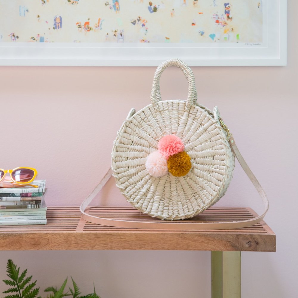 Sol Crossbody Circle Bag by Nomah Project, $150 - A sweet little circle bag, woven from palm and topped off with a perfectly coordinated trio of poms, this purse is virtually everything we love in a neat little package.