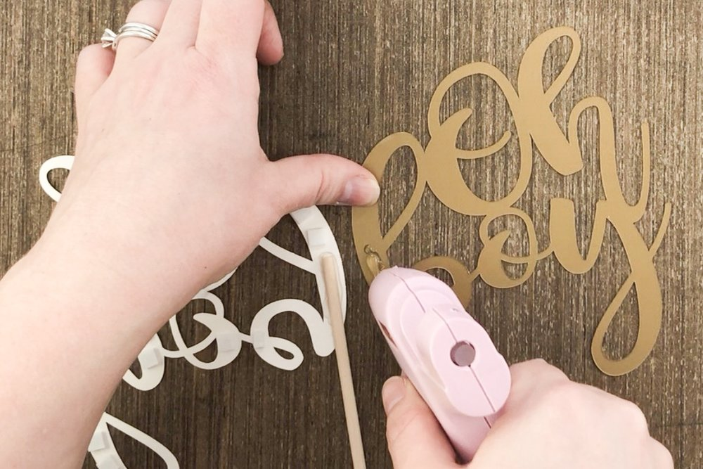 Hot glue is applied to the back cake topper piece cut with Cricut.jpg