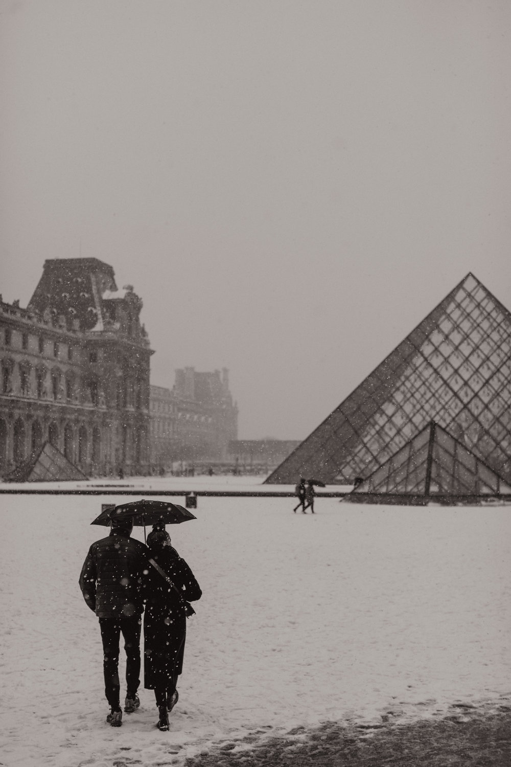 Two lovers in the snow in front of the Louvre. (PS. You can  buy this photo  as a fine art print!)