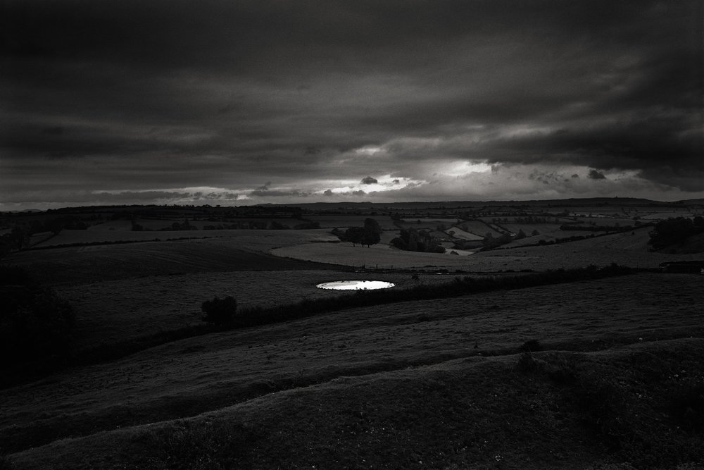 Lot 28: Don McCullin - Dew-pond by Iron Age hill fort,  Somerset, 1988