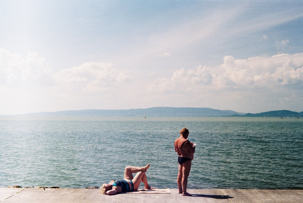 Two women basking in the summer sun at the lake's edge in Balatonfenyves, Hungary - 2018