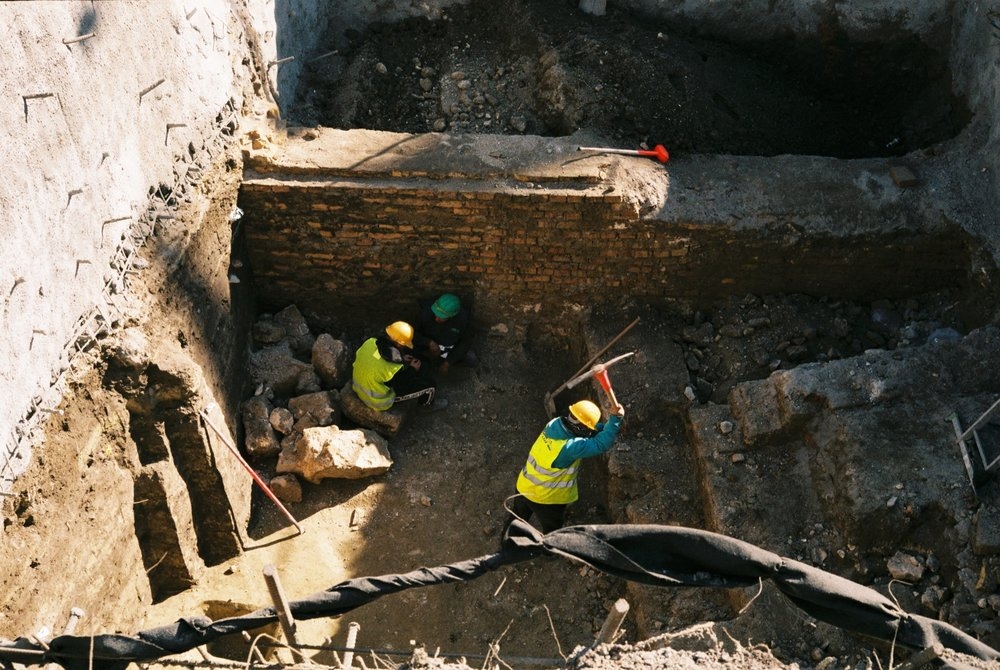 Two men rolls cigarettes as another breaks bricks with his pickaxe while at a construction site in Budapest, Hungary