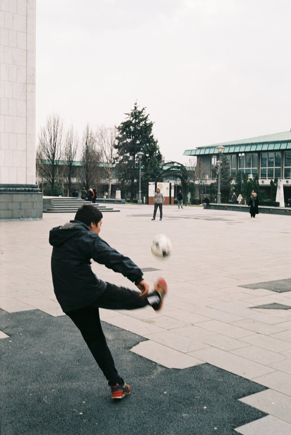 Two gypsy kids playing soccer outside the Temple of St. Sava