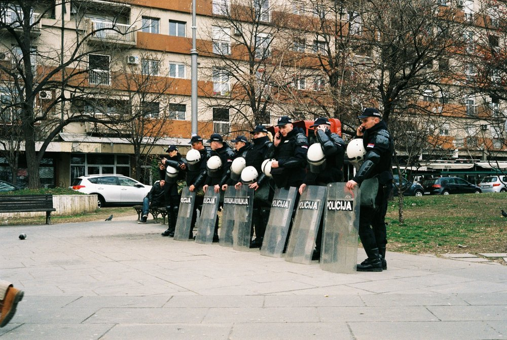 Serbian police prepare for crowd control while 2 Serbian football (soccer) teams compete nearby.
