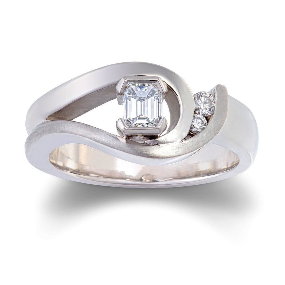 Palladium engagement ring set with one emerald cut diamond and two round brilliant cut diamonds - £2,460