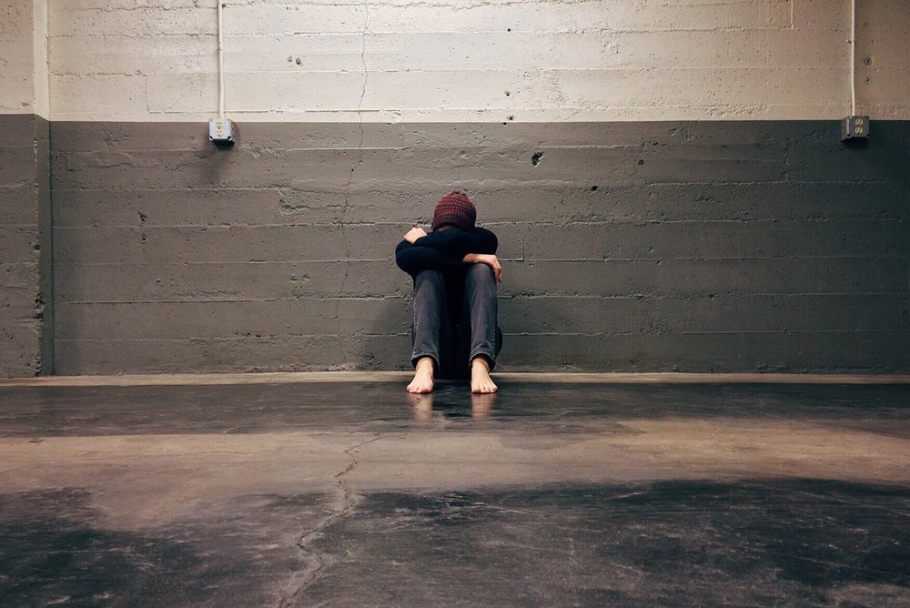 teen-hiding-face-shoeless-wall.jpg