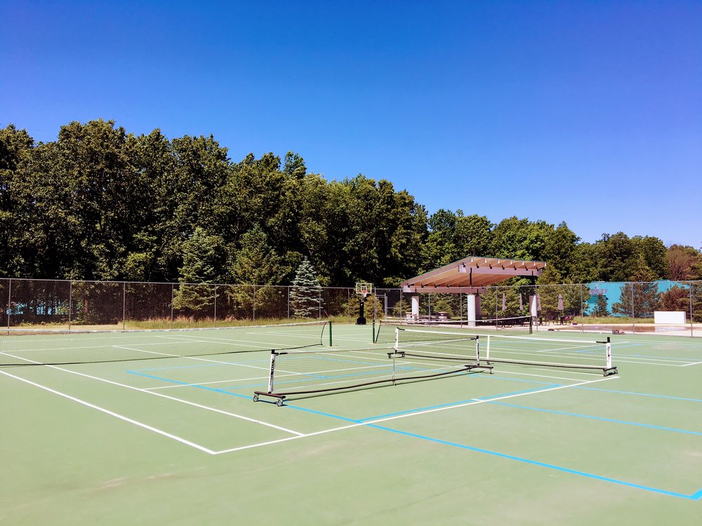 Two outdoor tennis courts with two pickle ball courts layed over the top.